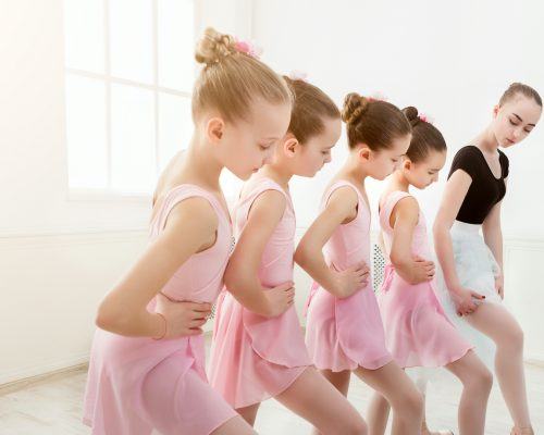 Young ballet teacher and students ballerinas in dance class. Girls are engaged in choreography in the ballet school, copy space