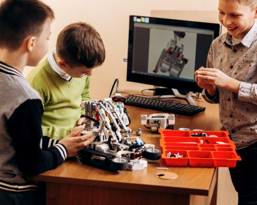 Three smart boys are making robots from the robotic constructor in the School of Robotics .